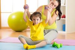 Frau hilft dem Kind, das Eignungsübungen mit Dummköpfen in der Turnhalle tut Stockfoto