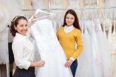 Frau hilft der Braut, wenn sie Brautkleid wählt Stockfotografie