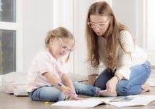 Frau hilft einem Kind zu zeichnen lizenzfreies stockbild