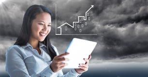 Frau hinter Aufflackern mit Tablette und weißes Hausdiagramm gegen stürmischen Himmel Stockfotografie