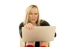 Frau hinter dem Laptopblick frustriert stockfoto