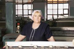 Frau hinter der Maschine an der Fabrik lizenzfreies stockfoto