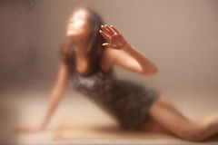Frau hinter Glas. Stockbilder