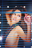 Frau hinter Vorhängen Lizenzfreie Stockfotos