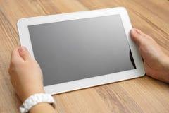 Frau hält Tablet-Computer auf Schreibtisch mit leerem Schirm Stockfotografie
