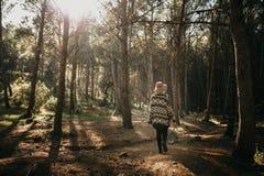 Frau in ihr einen Spaziergang mitten in einem Kieferwald zurück machend Stockfoto