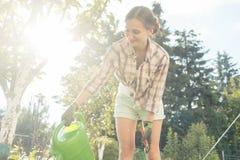Frau in ihrem Bewässerungsobstbaum des Gartens Lizenzfreies Stockfoto