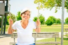 Frau in ihrem 50s auf dem Spielplatz Lizenzfreie Stockfotografie