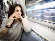 Frau in ihrem 30s reitet den U-Bahnamerikanischen nationalstandard, der heraus das Fenster schaut lizenzfreies stockbild
