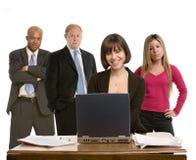 Frau an ihrem Schreibtisch mit Kollegen lizenzfreies stockfoto
