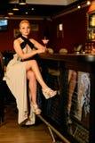 Frau im Abendkleid, das nahe Stangenzähler sitzt Stockfoto