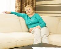 Frau im Alter, das auf Sofa sitzt Lizenzfreie Stockfotos
