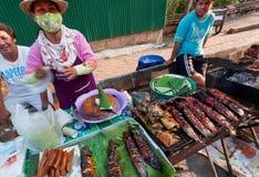 Frau im Antivirusmaskenfischrogen der Wels auf dem Grill während der Straße angemessen mit Fastfoodgericht Stockfotos
