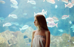 Frau im Aquarium, das durch das Glas auf Fischen schaut Lizenzfreie Stockfotografie