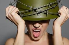 Frau im Armeesturzhelm mit Stacheldraht Lizenzfreies Stockfoto