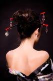 Frau im asiatischen Kostüm auf schwarzem Hintergrund. Lizenzfreies Stockbild