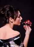 Frau im asiatischen Kostüm mit roten Blumen Stockfotos