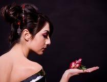 Frau im asiatischen Kostüm mit roten Blumen Lizenzfreies Stockfoto