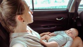 Frau im Auto mit einem schlafenden Baby in ihren Beinen stock footage