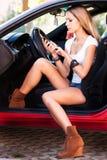 Frau im Auto mit Handy Lizenzfreie Stockfotos