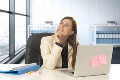 Frau im Büro, das an lächelndem glücklichem durchdachtem des Laptopcomputertischs und nachdenklich arbeitet Lizenzfreies Stockbild