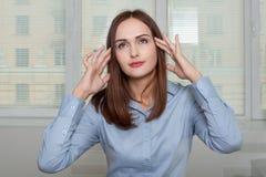 Frau im Büro hält Hände hinter seinem Kopf lizenzfreie stockbilder