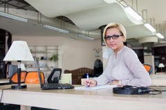 Frau im Büro mit einem Laptop Lizenzfreie Stockbilder