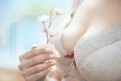 Frau im Büstenhalter, der Kirschblüte-Blume hält Stockfotografie