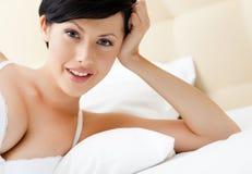 Frau im Büstenhalter liegt im Bett Stockfotografie