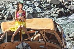 Frau im Baby - Puppenzauntritt, der in der Hand auf einem defekten Auto in der Sonne mit Teddybären sitzt Stockbild