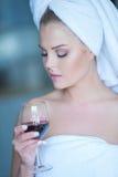 Frau im Bad-Tuch, das unten Glas Wein betrachtet Stockfotografie
