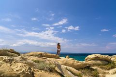 Frau im Badeanzug, der heraus zum Meer schaut Lizenzfreies Stockfoto
