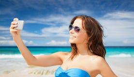 Frau im Badeanzug, der selfie mit smatphone nimmt Stockbilder