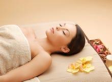 Frau im Badekurortsalon, der auf dem Massageschreibtisch liegt Stockfotos