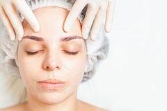 Frau im Badekurortsalon, der Gesichtsbehandlung mit Gesichtscreme bekommt Stockbilder