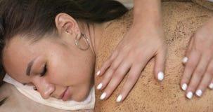 Frau im Badekurortsalon, der Massagetherapiekaffee trinkt sich zu scheuern stock video