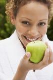 Frau im Bademantel, der frisches grünes Apple hält Lizenzfreie Stockfotografie