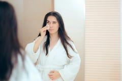 Frau im Bademantel, der ihr Gesicht mit Make-upentferner säubert Stockfotografie