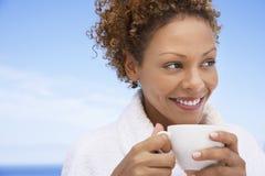 Frau im Bademantel, der Kaffee trinkt stockfotografie