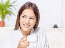 Frau im Bademantel, der sich zu Hause entspannt Stockbilder