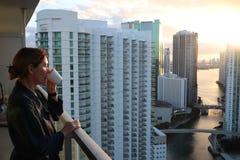 Frau im Bademantel ihren Morgenkaffee oder -tee auf einem im Stadtzentrum gelegenen Balkon trinkend Schöner Sonnenaufgang in im S lizenzfreies stockfoto