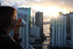 Frau im Bademantel ihren Morgenkaffee oder -tee auf einem im Stadtzentrum gelegenen Balkon trinkend Schöner Sonnenaufgang in im S lizenzfreies stockbild