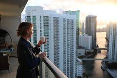 Frau im Bademantel ihren Morgenkaffee oder -tee auf einem im Stadtzentrum gelegenen Balkon trinkend Schöner Sonnenaufgang in im S stockbilder