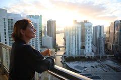Frau im Bademantel ihren Morgenkaffee oder -tee auf einem im Stadtzentrum gelegenen Balkon trinkend Schöner Sonnenaufgang in im S lizenzfreie stockfotos