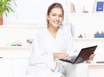 Frau im Bademantel mit Computer Stockfoto