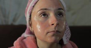 Frau im Bademantel mit Gesichtsmaske Aufpassen eines Sp?t- Films an Fernsehen stockfotos