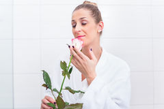 Frau im Bademantel mit Weißrose Stockbild