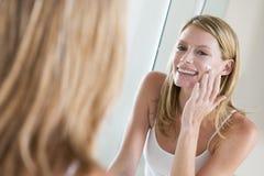 Frau im Badezimmer, das Gesichtssahne aufträgt Stockbild