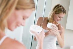 Frau im Badezimmer, das Lotion anwendet Stockbilder