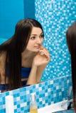 Frau im Badezimmer hinter dem Spiegel Lizenzfreies Stockfoto